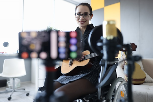 Smiling woman is recording guitar playing online lessons for teaching music concept