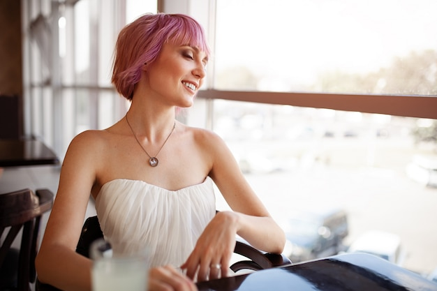 Smiling woman is sitting in comfortable cafe-bar during her recreation time