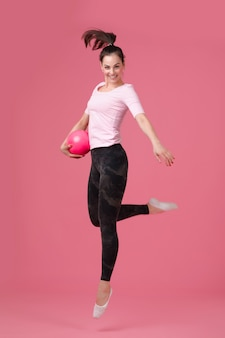 Smiling woman jumping with the ball