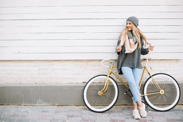 Smiling woman leaning on bicycle near wall