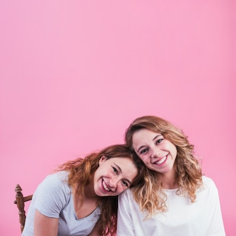 Smiling woman leaning head on her friend's shoulder against pink backdrop