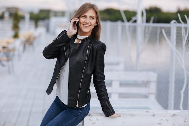 Smiling woman leaning on a white wooden board talking on the phone
