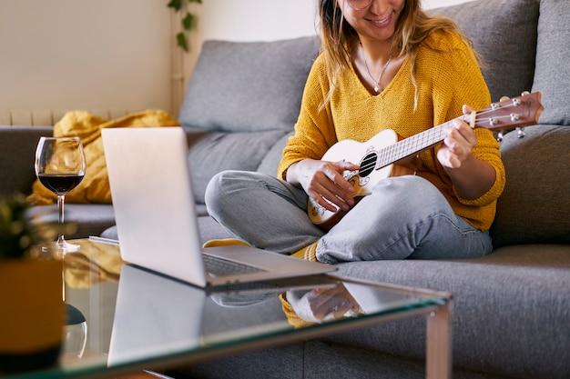 Улыбающаяся женщина учится играть на укулеле онлайн со своего ноутбука.