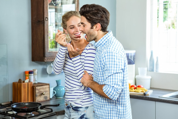 Smiling woman letting man taste a sauce with a wooden spoon