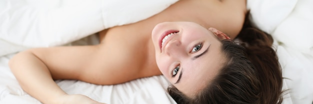 Smiling woman lies in bed wake up early in the morning in good mood