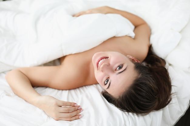 웃는 여자는 침대에 놓여 있습니다. 좋은 기분으로 아침 일찍 일어나