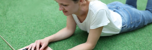 웃는 여자는 노트북으로 푸른 잔디에 누워