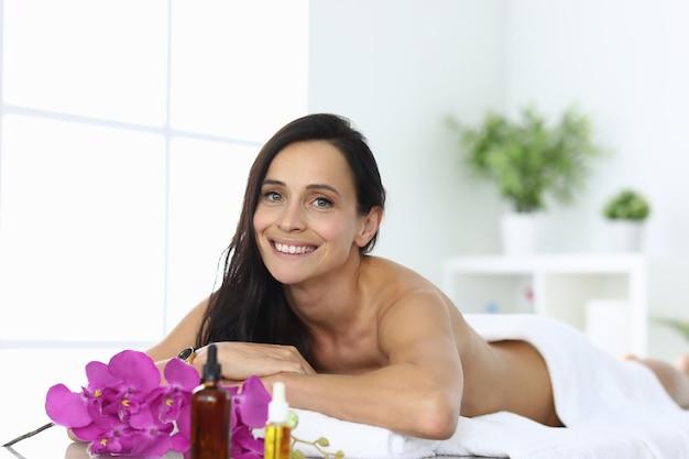 笑顔の女性がスパセンターのクローズアップのマッサージテーブルに横たわる