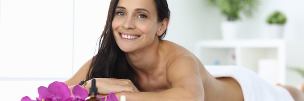 笑顔の女性がスパセンターのマッサージテーブルに横たわっています。スパトリートメントとあらゆるタイプのマッサージコンセプト