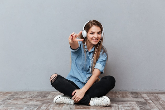 Smiling woman listening music on the floor