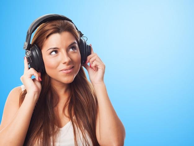 Donna sorridente che ascolta musica in cuffia