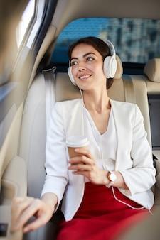 Улыбающаяся женщина слушает музыку в такси