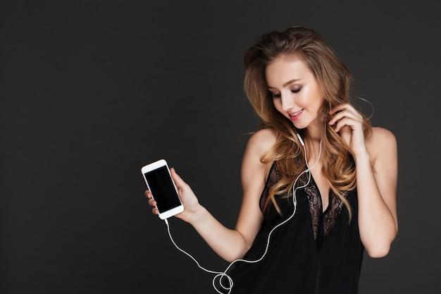 空白の画面の携帯電話で音楽を聴いて笑顔の女性