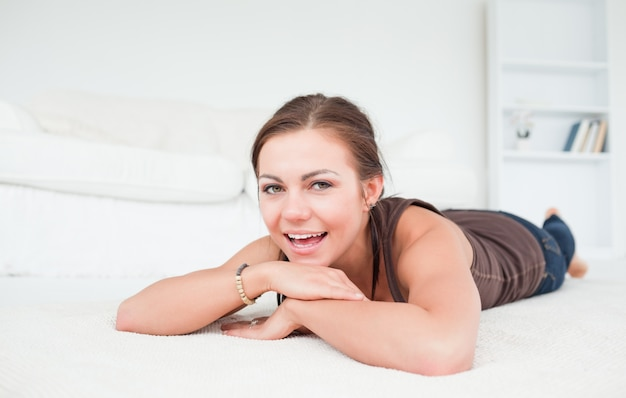 Smiling woman liying on a carpet