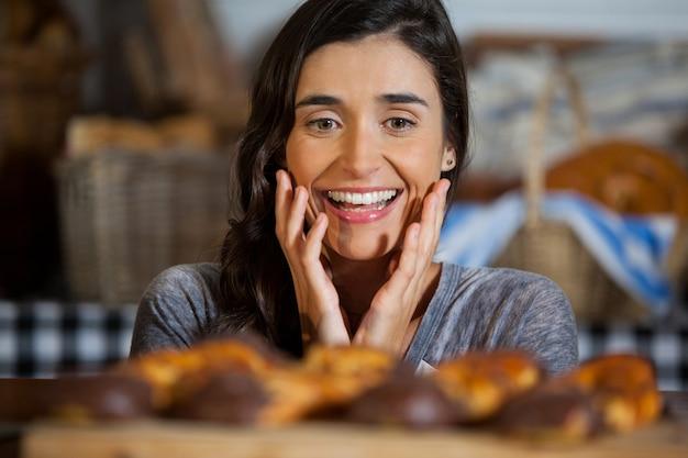 Улыбающаяся женщина, глядя на хлеб в прилавке