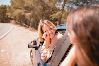 Smiling woman looking at friend in car