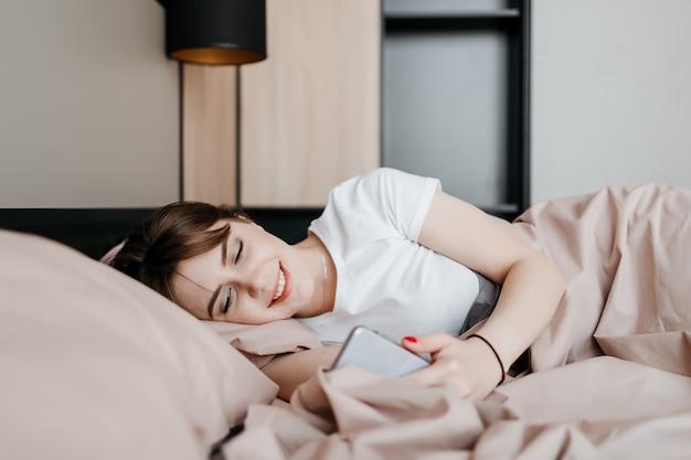 집에서 침대에서 아침에 전화 화면을보고 웃는 여자