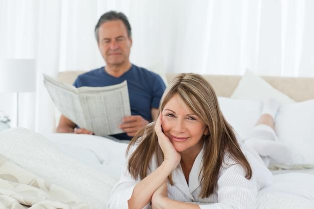 그녀의 남편이 읽는 동안 카메라를보고 웃는 여자