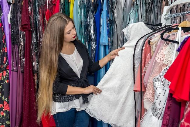 의류 매장에서 드레스를 찾고 웃는 여자