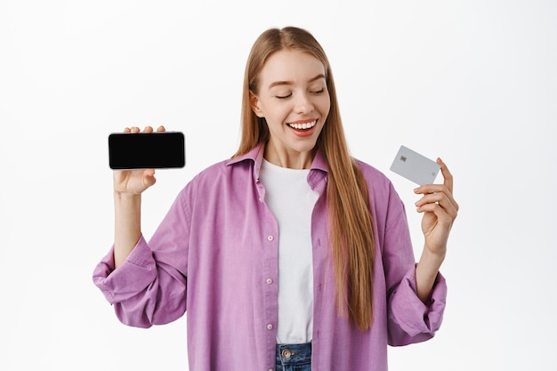 Smiling woman looking happy at her credit card, showing horizontal smartphone screen, recommend application or internet store, standing over white wall