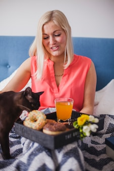 Smiling woman looking at her cat next to her breakfast