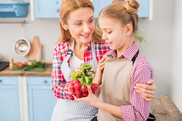 Smiling woman looking at her daughter holding fresh radish in hand