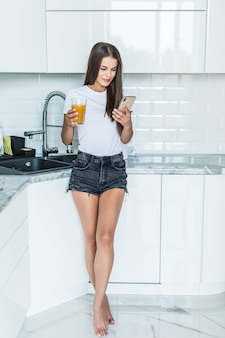 Smiling woman looking at mobile phone and holding glass of orange juice in a kitchen