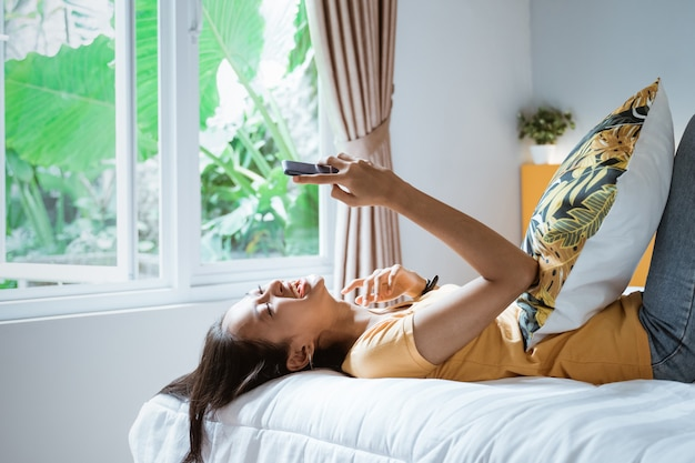 Smiling woman looking at mobile phone lying down on white bed.