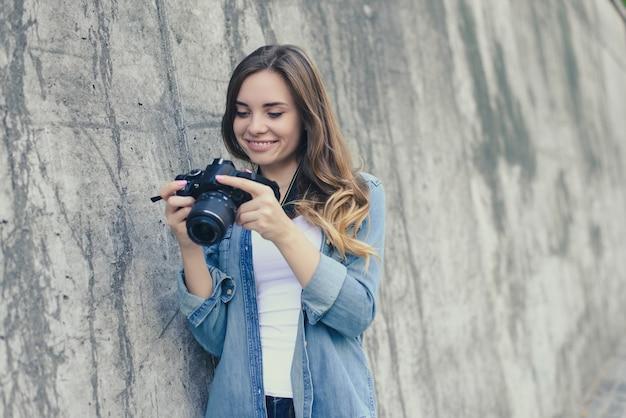 カメラの灰色の壁の背景を見ている笑顔の女性
