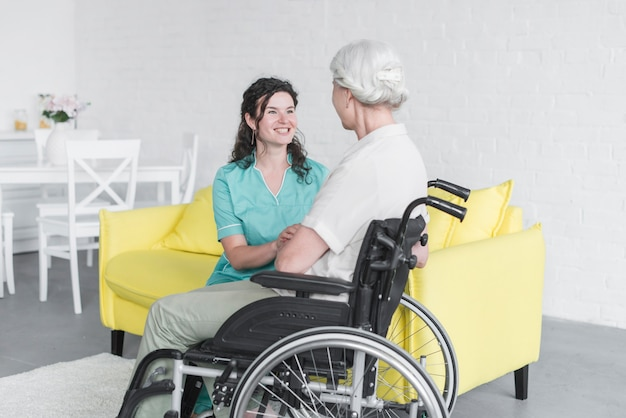 Smiling woman looking at senior woman sitting on wheel chair