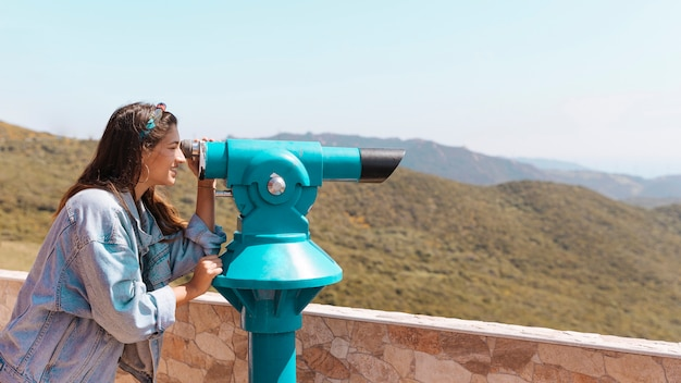 Smiling woman looking through spyglass