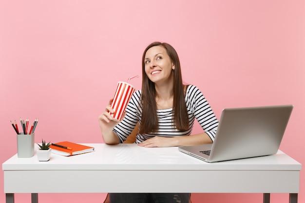 콜라나 탄산음료가 있는 플락틱 컵을 들고 꿈을 바라보며 웃고 있는 여성은 파스텔 핑크색 배경에 격리된 현대적인 pc 노트북과 함께 흰색 책상에서 일합니다. 성취 사업 경력입니다. 공간을 복사합니다.