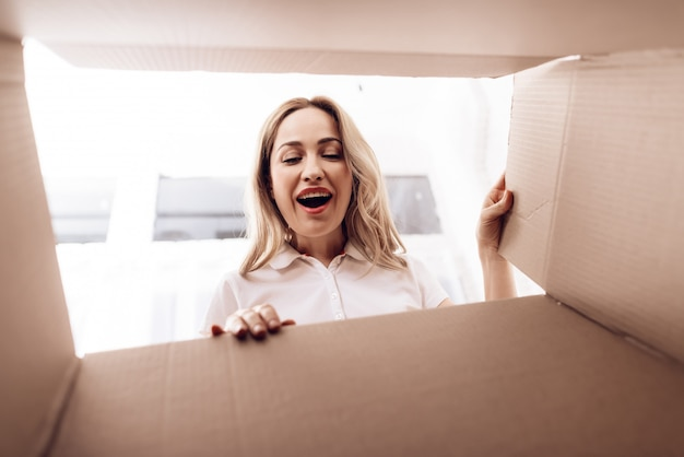 Smiling woman looks into empty box from inside.