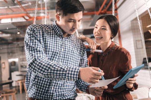 Улыбающаяся женщина. любящая улыбающаяся женщина в стильной блузке обнимает своего мужчину во время совместной работы