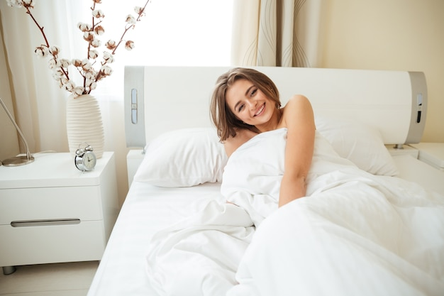 Smiling woman lying on the bed under blanket and  at home