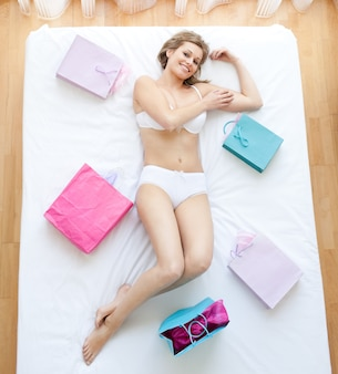 Smiling woman lying on a bed surrounded with shopping bags