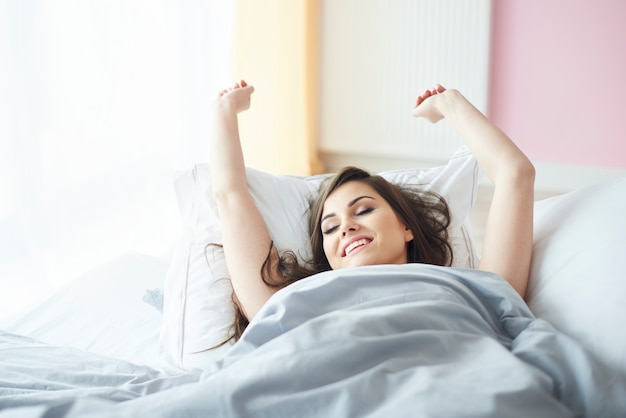Smiling woman lying on the bedroom