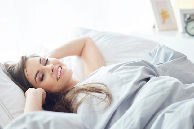 Donna sorridente sdraiata in camera da letto