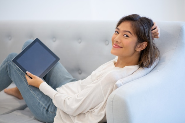 Smiling woman lying on coach with pc tablet and touching hair
