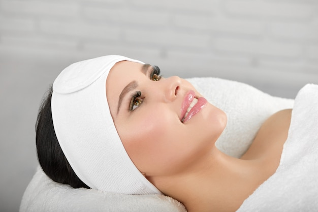 Smiling woman lying on cosmetological coach