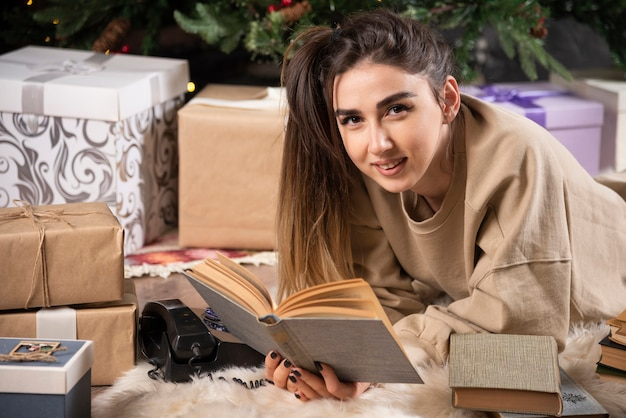 Donna sorridente sdraiata su soffice tappeto con libri.