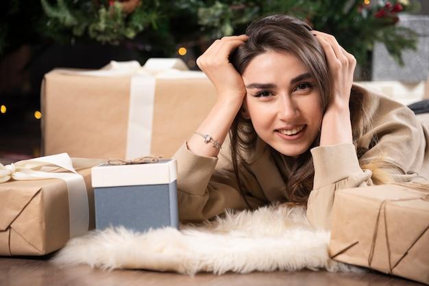 Donna sorridente sdraiata su soffice tappeto con regali di natale.