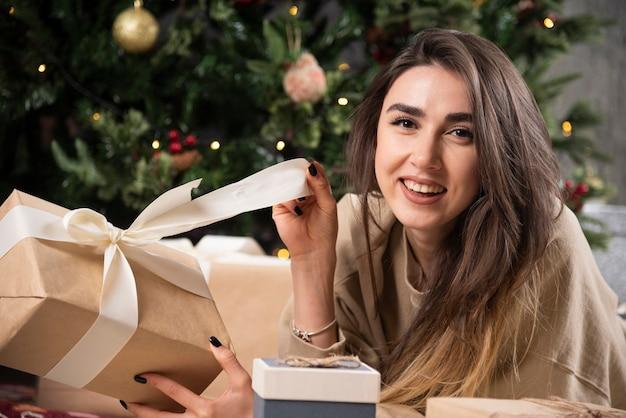 Donna sorridente sdraiata su un soffice tappeto e avvolgendo un regalo di natale.