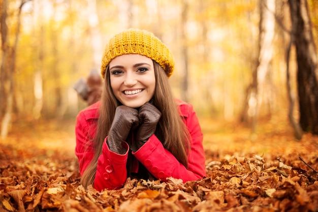 紅葉に横たわって笑顔の女性