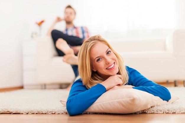 Улыбающаяся женщина, лежа на ковре дома