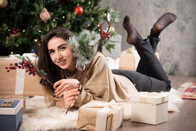 クリスマスプレゼントとふわふわのカーペットの上に横たわっている笑顔の女性。