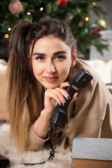 電話でふわふわのカーペットの上に横たわっている笑顔の女性。