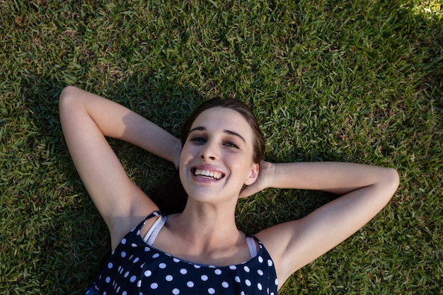 Smiling woman lying on grass with hands behind head