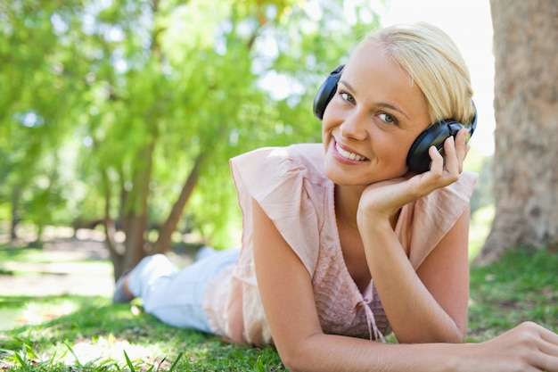 Smiling woman lying on the lawn while wearing headphones