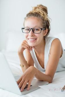 Улыбающаяся женщина, лежащая на кровати и работающая на ноутбуке